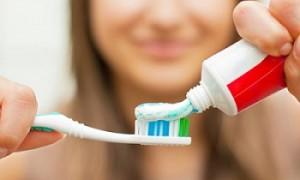 Mulher desfocada colocando creme dental na escova de dentes